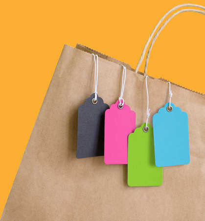 Colorful price tags with rope hanging out of brown shopping bag.