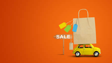 Yellow car with shopping paper bag from a sale on the roof