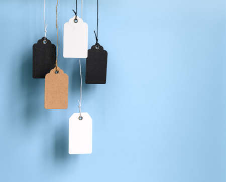 Blank cardboard price tags tied with rope on blue background