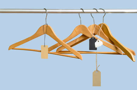 Empty hangers with price tags after a sell-off in the store on blue background. Big final sale concept