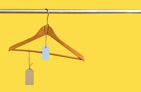 Empty coathanger with price tags in the store on yellow sale background. Major sell-off concept