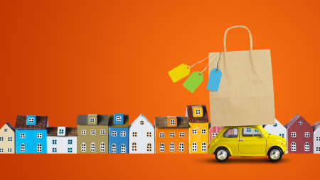 Yellow toy car with shopping paper bag on the roof returns from the store sale on orange background with miniature houses