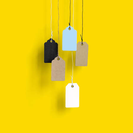 Blank price tags hang on ropes on a yellow background Sale concept