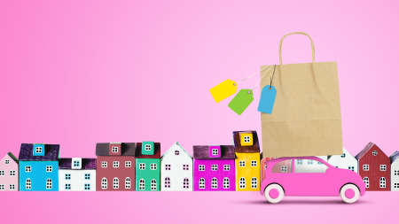 Pink toy car with shopping paper bag on the roof returns from the store sale on pink background with miniature houses