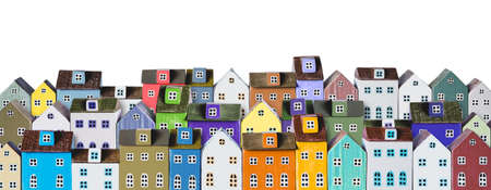 Colorful miniature houses arranged in a rows isolated on a white background. Urban city background banner. Copy space