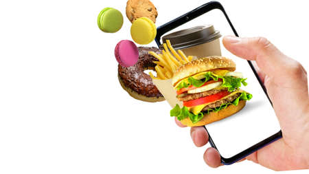Hand holding phone with hamburger french fries coffee cup donuts flying out of the screen isolated on white background. Online ordering fast food.