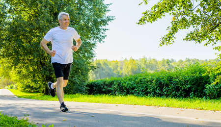 Active mature man running in park during morning workout at springtime.