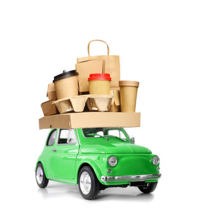 Retro green toy car delivering fast food order - various take-out food containers, pizza box, coffee cups in holder and paper bag isolated on white