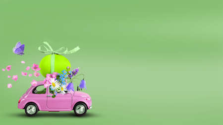 Pink retro toy car carrying an easter egg and flowers bunch on a green background. Copy space