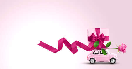 Pink toy car with gift box on a roof and rose flower on a pink background. Copy space.