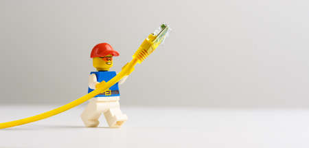 Technician toy man holding yellow network cable. Standard-Bild