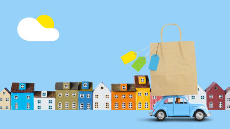 Blue car with shopping paper bag on the roof