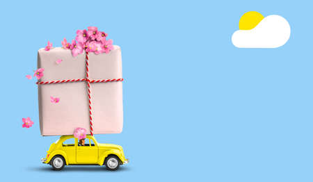 Yellow car with gift box on a roof with flowers on blue background. Standard-Bild