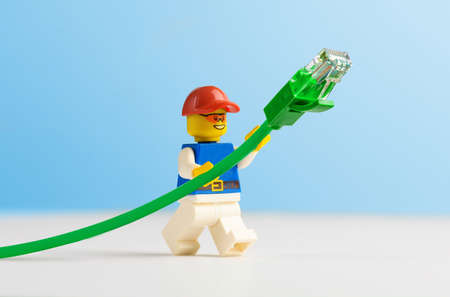 Minifigure Technician holding green network cable.
