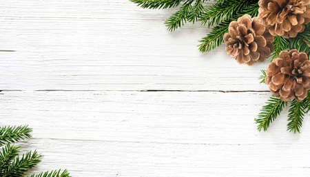 Christmas tree branches and pine cones on white wood background