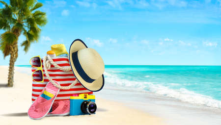 Summer beach bag and accessories - straw hat, flip flops and sunglasses on sandy beach and azure sea on background