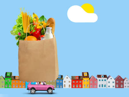 Pink car with shopping paper bag with groceries on the roof on city background 写真素材