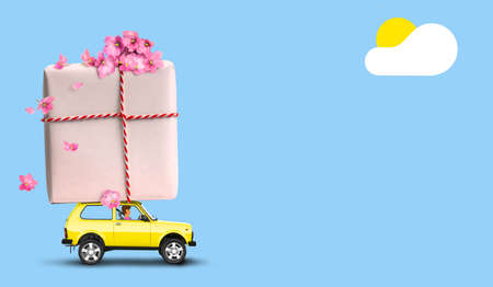 Yellow car with gift box on a roof with flowers on blue background. 写真素材