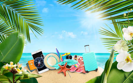 Summer tropical background of accessories for travelers on a sandy island surrounded by tropical palm leaves and flowers.