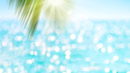 Green blur palm leaf on ocean with bokeh sun light background.
