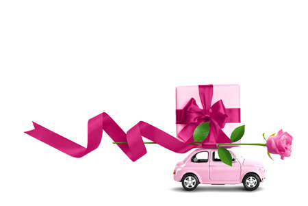 Pink toy car with gift box on a roof and rose flower isolated on a white 写真素材