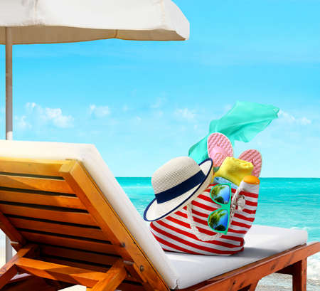 Beach bag with accessories on sun lounger on the beach