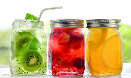 Bright Colorful refreshing summer drinks in glass jars with ice on white background