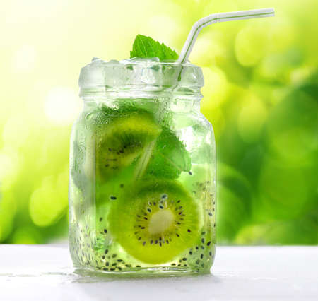 Kiwi cocktail drink with chia seeds in glass jar