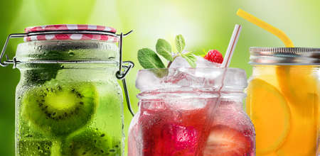 Bright Colorful refreshing summer drinks in glass jars with ice on a white background 写真素材