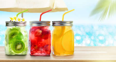 Summer refreshing exotic drinks cocktails in glass jars with straws on seascape with bokeh sun light background. 写真素材