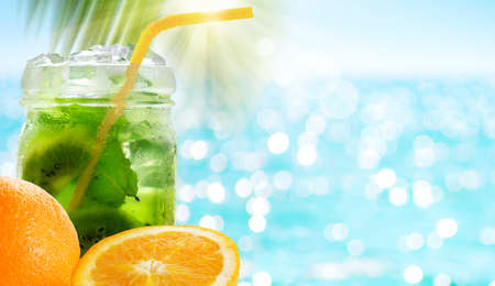 Kiwi cocktail drink with mint leaves in glass jar and orange fruit