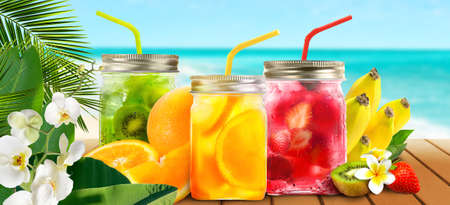 Summer refreshing exotic drinks cocktails in glass jars with tropical fruits on wooden table on seascape background.