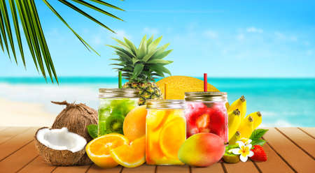 Tropical fruits with fresh juice cocktails in mason jars on wooden table on sand beach and sea background.