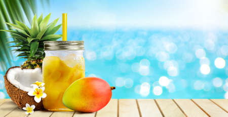 Summer tropical cocktail drink of mango fruit and coconut juice on blue turquoise sea background