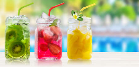 Summer refreshing exotic drinks cocktails in glass jars with straws on wooden counter on swiming pool background. 写真素材