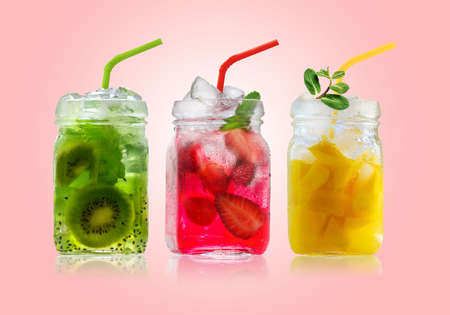 Bright Colorful refreshing summer drinks in glass jars and straws on a pink background 写真素材