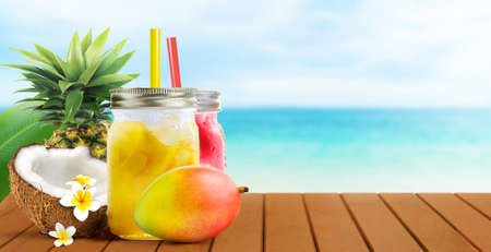 Summer tropical cocktail drinks of mango coconut juice and strawberry on blue turquoise sea background