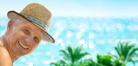 Man have fun, smiling to the camera, relaxing by the sea beach on blue turquoise sea background.