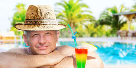 A man is enjoying his vacation relaxing with refreshing drink on the pool on resort hotel background. 写真素材