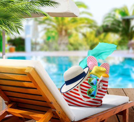 Beach bag with accessories on sun lounger near swimming pool in luxury resort
