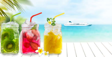 Summer cold exotic drinks cocktails in glass jars with straws on seascape with cruise ship background.