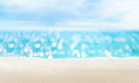 Seascape and sandy beach. Defocused sea water surface glittering on the sun.