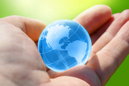 Blue Glass globe of the planet Earth in human hand Banco de Imagens