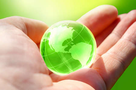Green Glass globe of the planet Earth in human hand