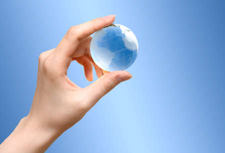 Blue Glass globe of the planet Earth in female hand