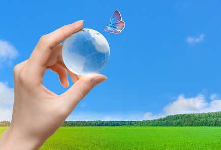 Glass globe of the planet Earth in human hand and flying butterfly