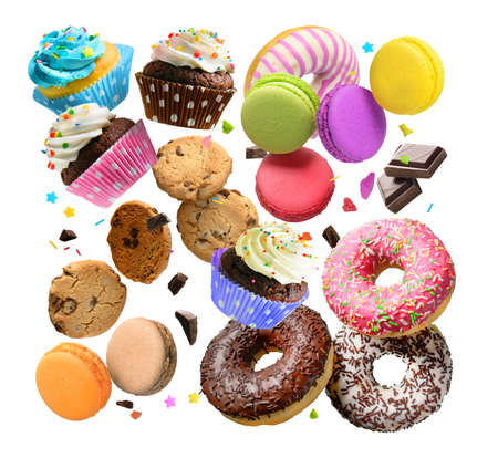 Confectionery and sweets collage. Donuts, cupcakes, cookies, macarons flying over white background. Banco de Imagens
