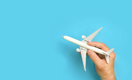 Male hand holding aircraft model, airplane in hand on blue background. Banco de Imagens