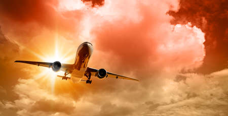 Airplane in the sky at sunset on dramatic crimson cloudy sky background Banco de Imagens