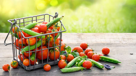 Tomatoes and green peas in metal basket on wooden rusrik table Banco de Imagens
